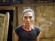 An elderly Laoseng woman smokes tobacco in a pipe in the recently temporarily relocated village of Ban Watai, Phongsaly province, Lao PDR. Ban Watai will be joined with three other Laoseng villages following the construction of the Nam Ou Cascade Hydropower Project Dam 6.