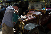 A driver tops-up the radiator of a visiting vintage car in the centre of a French village, during a three-day rally journey through the Corbieres wine region, on 26th May, 2017, in Lagrasse, Languedoc-Rousillon, south of France. Lagrasse is listed as one of Frances most beautiful villages and lies on the famous Route 20 wine route in the Basses-Corbieres region dating to the 13th century.