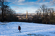 A man walks in the snow, Queens Park, Glasgow.  The park is known for its view across the south side of Glasgow, with a snow covered Campsie Fells in the background.