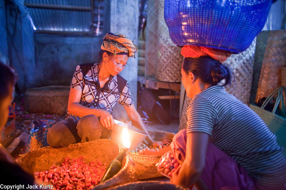 25 APRIL 2010 - PAYANGAN, BALI, INDONESIA: A woman sells shallots by torchlight in the market in Payangan, Bali. Many Indonesians shop every day because they don't have refrigerators in their homes.  PHOTO BY JACK KURTZ