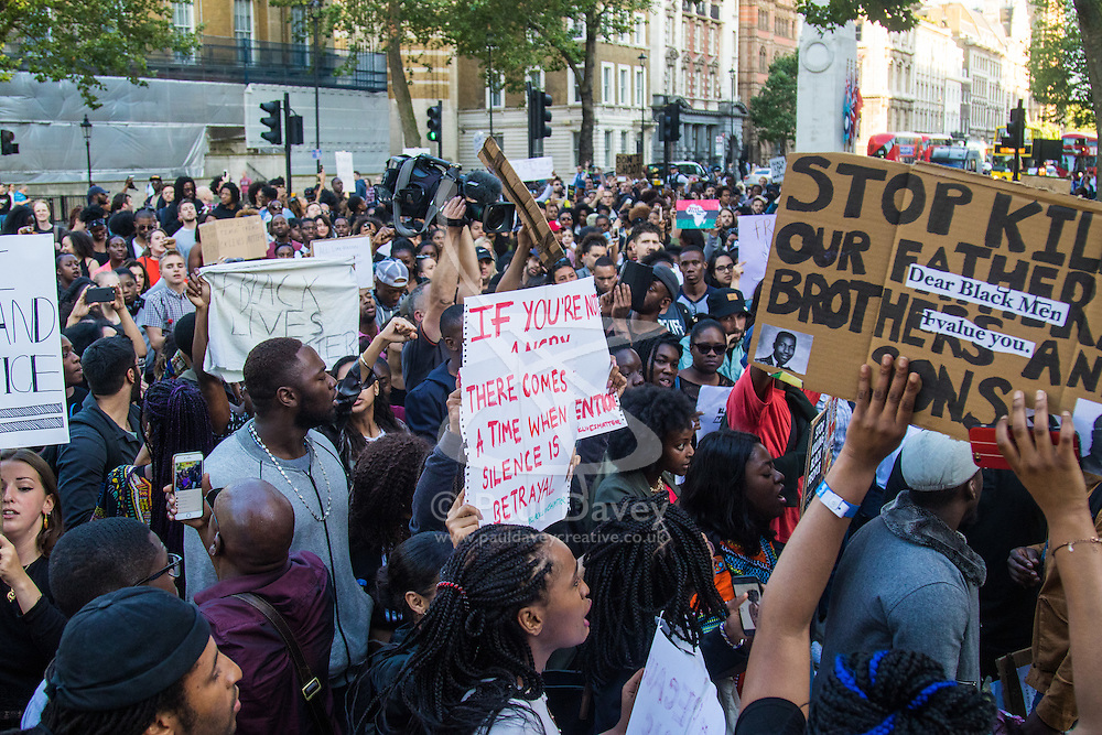 """London, July 8th 2016. Hundreds gather on London's Southbank before marching through the streets of London to Parliament Square, Downing Street and the BBC, in a Black Lives Matter protest in solidarity with Americans following the shooting dead of two black men, Philando Castile in Minnesota and Alton Sterling in Louisiana by police in the US. PICTURED: The crowd chants """"Hands up! Don't Shoot!"""" outside the gates of Downing Street."""