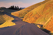Twisting s-turn curves on mountain road on rolling green hills at sunset in spring, Bolinas Ridge, Mount Tamalpais, Marin County Coast, California Twisting curves on rural country mountain road at sunset, Bolinas Ridge, Mount Tamalpais, Marin, California