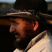 Weslaco Rodeo Club coach Frank Quesada watches over his students as the sun sets on his ranch north of Weslaco. Quesada, an art teacher at Weslaco High School, has also taught students how to ride bulls since he started the club 33 years ago. <br /> Nathan Lambrecht/The Monitor