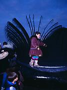Young girl from Barrow walking along baleen of Bowhead Whale just pulled ashore, Arctic Ocean Coast at Barrow, Alaska.