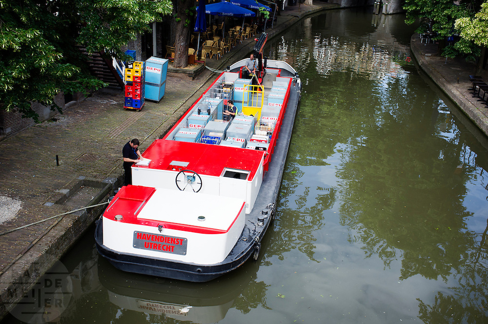 Een boot bevoorraadt de horecagelegenheden aan de Oudegracht in Utrecht.<br /> <br /> A boat is delivering the goods for the restaurants at the Oudegracht in Utrecht.