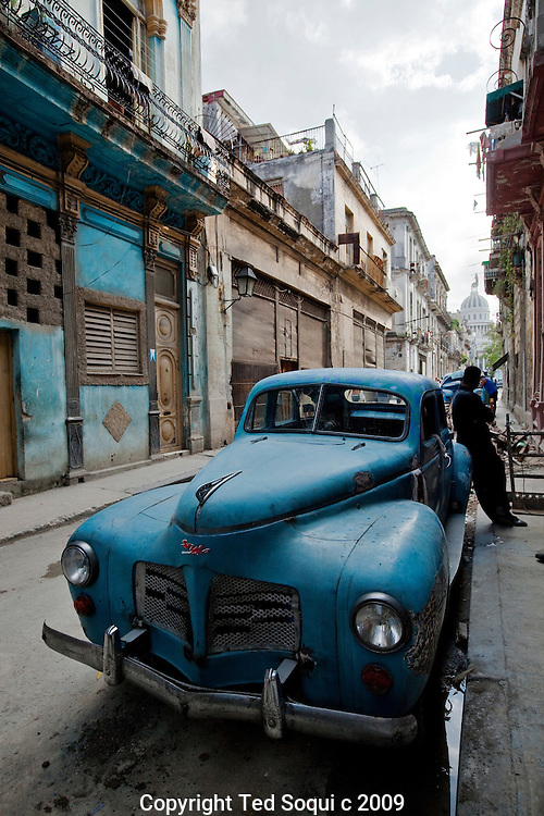 An old American car from the late 1950's parked on a old Havana street. Cuba was the largest importer of US cars before the revolution in 1959. .Cars ownership in Cuba is still considered a luxury item, many are used to ferry tourist around for about $50 dollars a day. The average Cuba makes 15-20 dollars per month. These old cars are now retrofitted with 4 cylinder diesel engines instead of their original V8 gas burning engines. .Cuban ingenuity have kept many of these vehicles running way beyond their original life span.