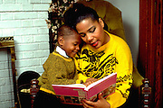 Mother age 38 reading to 6 year old son in their home.  St Paul Minnesota USA