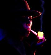 Woman with glowing corn cob pipe.Black light