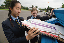 Secondary school students recycling old cardboard boxes in school recycling bin,
