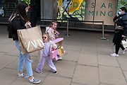 On the day that the UK government eased Covid restrictions to allow non-essential businesses such as shops, pubs, bars, gyms and hairdressers to re-open, an adult and two young girls walk past John Lewis on Oxford Street, on 12th April 2021, in London, England.