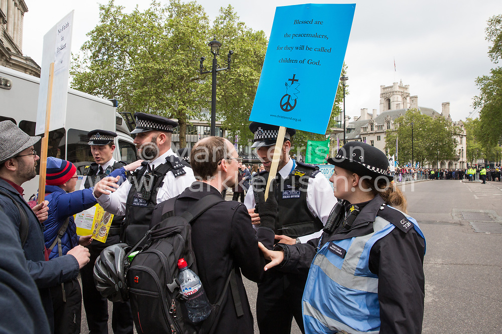 London, UK. 3 May, 2019. Campaigners from the Peace Pledge Union and faith groups are contained by police officers as they protest outside Westminster Abbey against the holding of a National Service of Thanksgiving to mark fifty years of the Continuous at Sea Deterrent (CASD) attended by dignitaries including the Duke of Cambridge and the newly appointed Defence Secretary Penny Mordaunt.