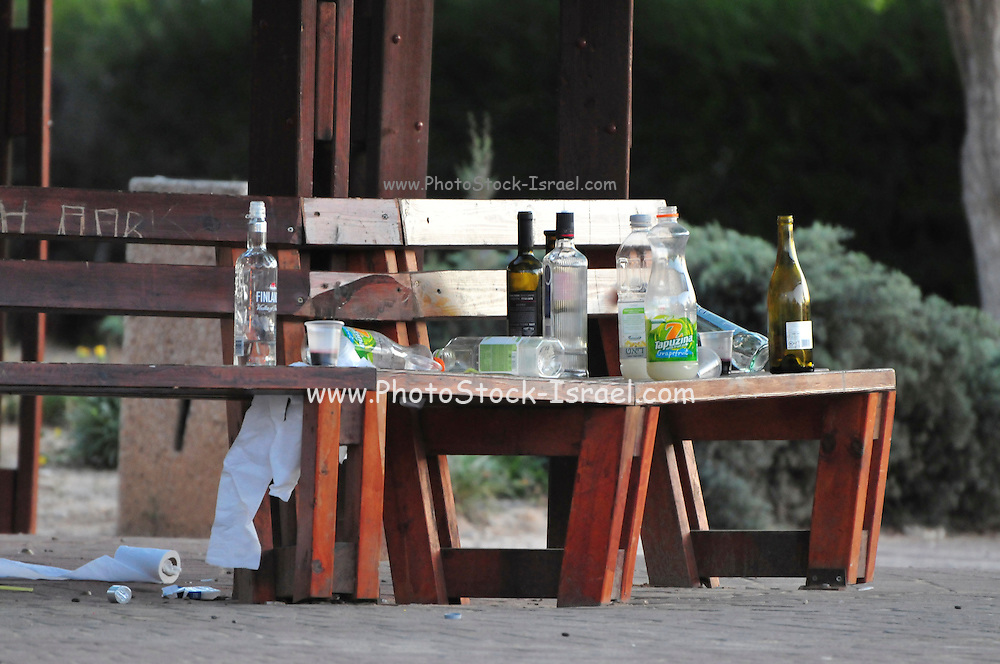 Israel, Haifa, Empty alcohol bottles on a park bench. Alcohol consumption by teenagers and youth has become a big concern to law enforcing agencies in Israel. With laws regulating alcoholic consumption by minors most of this consumption is done outdoors in parks such as this