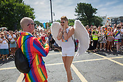 A man wearing a rainbow suit proposes to his male partner who is dressed as a white angel during the Brighton Pride parade on the 4th August 2018 in the United Kingdom. Brighton Pride is an annual event held in the city of Brighton and Hove, England, organised by Brighton Pride, a community interest company who promote equality and diversity, and advance education to eliminate discrimination against the lesbian, gay, bisexual and transgender community.