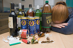 Upset woman surrounded by a selection of drugs and alcohol,