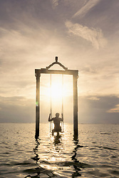 Rear view of woman sitting on rope swing at beach against sunset, Gili Trawangan, Lombok, Indonesia