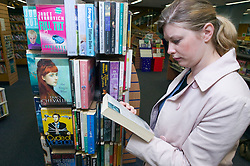 Young woman looking at a book in a library,