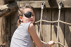 Portrait of a girl climbing on rope in adventure playground, Bavaria, Germany