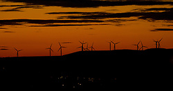 © Licensed to London News Pictures . FILE PICTURE DATED 08/10/2012 . Oldham , UK. Wind turbines silhouetted against a moody sky in moors over Oldham just after the sun has set . Oldham has been named England's most deprived town by the Office for National Statistics today (18th March 2016) . Photo credit : Joel Goodman/LNP
