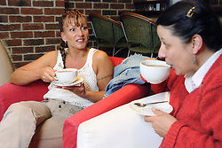 Two women sitting in bar drinking cappuccinos,