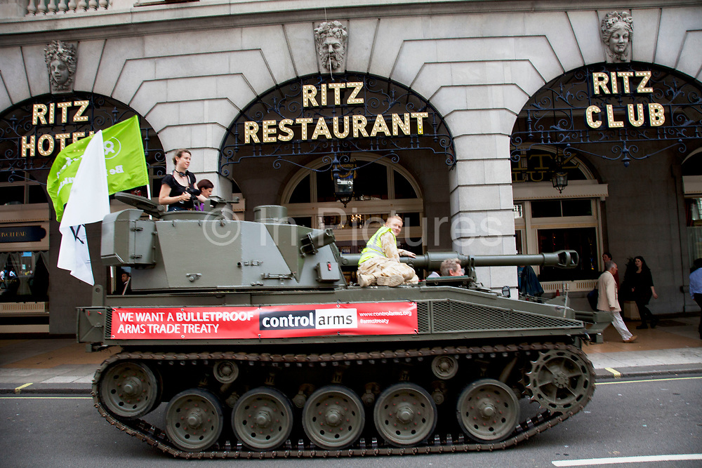 Tank passing the Ritz Hotel on Piccadilly. Campaigners and supporters from Oxfam and Amnesty International, as part of the Control Arms coalition, drive an Abbot gun tank around central London to highlight the need for a global Arms Trade Treaty (ATT) to be agreed during a United Nations conference next month (July 2012). London, England, UK. 27th June 2012.