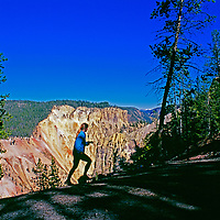 A runner jogs on a trail above the Grand Canyon of the Yellowstone River.
