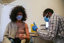© Licensed to London News Pictures. 25/06/2021. London, UK. 19 year old Chloe Lacour gestures as vaccinator Ahmed Said administers the first dose of the Pfizer Covid-19 vaccine in Tottenham, north London. Londoners are urged to get Covid-19 vaccine this weekend. Photo credit: Dinendra Haria/LNP