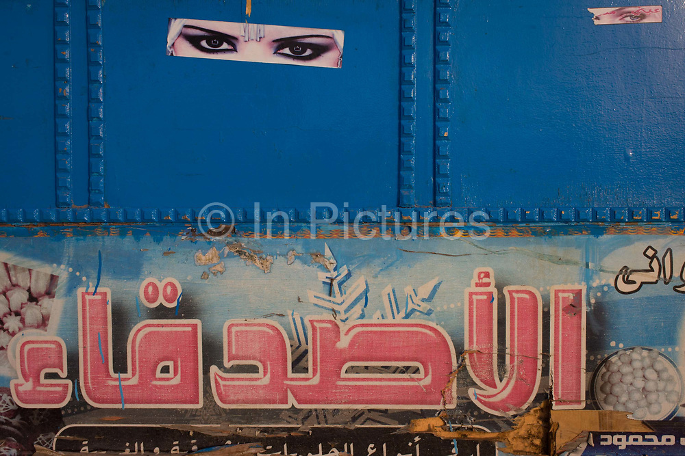 Detail of a street food stall in Bairat on the West Bank of Luxor, Nile Valley, Egypt. Pairs of eyes seemingly peer through the blue side of the stall cart located opposite the state-run ferry and Arabic lettering is seen at the bottom.