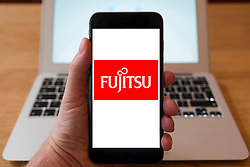 Using iPhone smartphone to display logo of Fujitsu,  Japanese multinational information technology equipment and services company