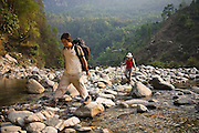 Liana Welty and her guide Bibek Gurung cross the Bhurungdi Khola River below Hille, Annapurna Himalaya, Nepal.