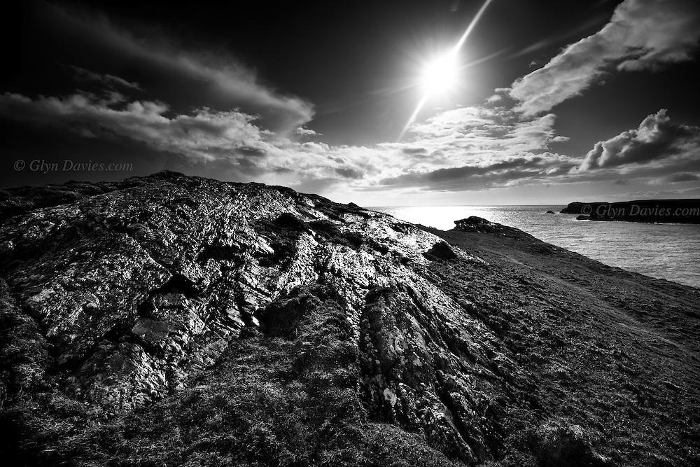 Intense sunshine illuminates wet rocks after heavy rain on the headland at Porth Dafarch, Holy Island, West Anglesey
