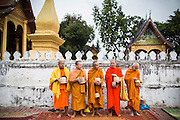 """11 MARCH 2013 - LUANG PRABANG, LAOS: Visiting Buddhist monks wait for Lao monks to pass them during the tak bat in Luang Prabang. The """"Tak Bat"""" is a daily ritual in most of Laos (and other Theravada Buddhist countries like Thailand and Cambodia). Monks leave their temples at dawn and walk silently through the streets and people put rice and other foodstuffs into their alms bowls. Luang Prabang, in northern Laos, is particularly well known for the morning """"tak bat"""" because of the large number temples and monks in the city. Most mornings hundreds of monks go out to collect alms from people.     PHOTO BY JACK KURTZ"""