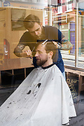 A fashionable man has a haircut in a barber shop on Brick Lane, London, UK