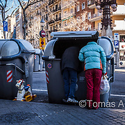 Gaudí Avenue. A couple recycling food from a garbage container where a fast food shop is throwing out their expired products.
