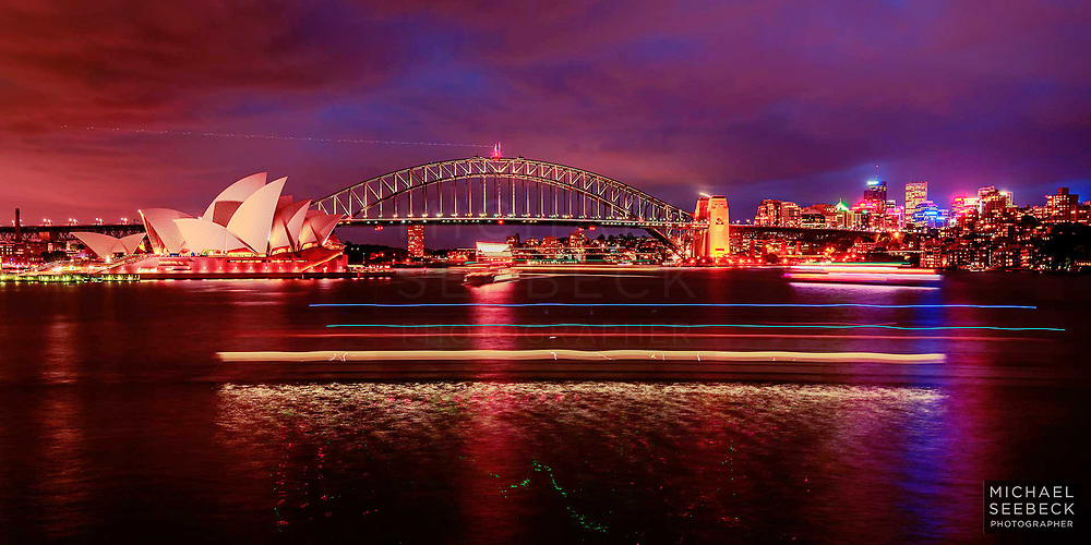 Party boats and ferries cruise past Sydney Opera House and Sydney Harbour Bridge, on Sydney Harbour, in twilight.<br /> <br /> Code: BANM0004<br /> <br /> Limited Edition Print