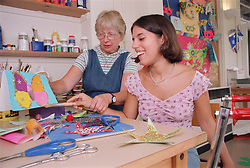 Carer assisting teenage girl to use paintbrush during art lesson in residential respite care home,