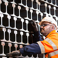 British Steel - worker inspecting rail tracks stacked up