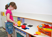 Preschool girl of 5 plays with a toy kitchen
