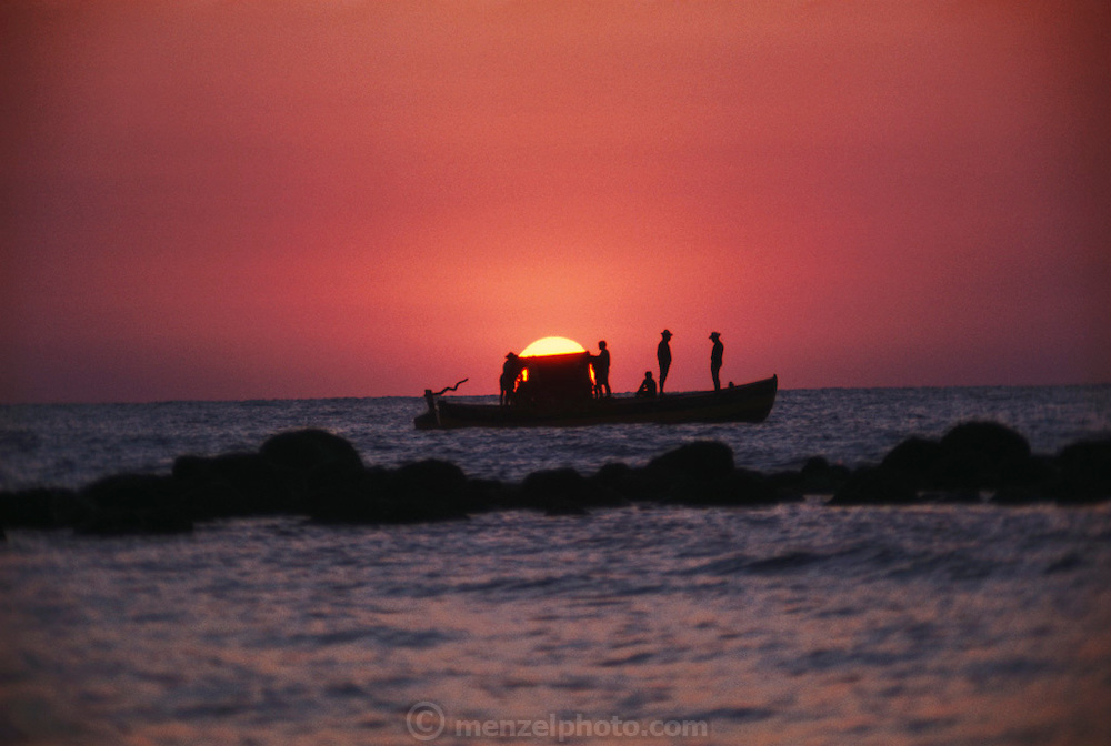 Sunrise behind a fishing boat with fishermen silhoutted, Veracruz, Mexico.