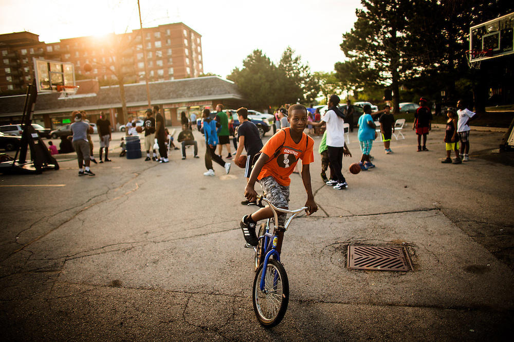 Mississauga , Ontario - August 19, 2015 -- Basketball -- A teen rides his bike in front of a temporary basketball court set up by the Erin Mills Youth Centre during a community event in a parking lot in Mississauga, Thursday August 19, 2015   (Mark Blinch for the Globe and Mail)
