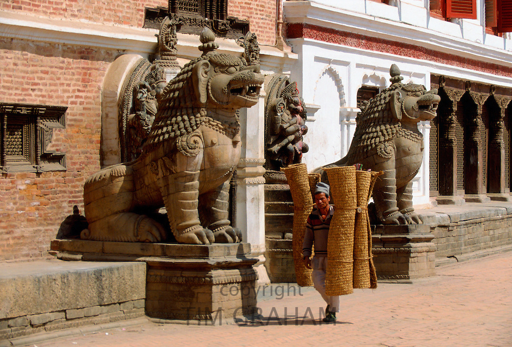Man carrying coir rugs through the street past ancient statues in Bhaktapur, Nepal