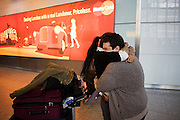 """Amid the hectic arrivals concourse of Heathrow airport's Terminal 5, two friends hold on to each other tight after an international arrival. Standing in front of a Mastercard ad which shows scenes of London, the coupe squeeze each other tight amid an otherwise hectic airport concourse in heathrow's Terminal 5. They have clearly missed each other after such a break apart but are otherwise oblivious to the crowds that surround them in this busy international airport. They embrace with genuine affection for each other in a display of sexual freedom that is otherwise seen as a taboo in other countries. From writer Alain de Botton's book project """"A Week at the Airport: A Heathrow Diary"""" (2009)."""