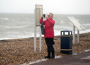 © Licensed to London News Pictures. 11/11/2014. Southsea, UK. A woman takes a photograph in the wind. Wet and windy weather today, 11 November 2014, at Southsea, Portsmouth. The Met Office have issued weather warnings in some parts of the UK. Photo credit : Stephen Simpson/LNP