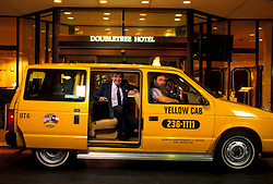 Businessman Getting Out of a taxi cab at the entrance of the Doubletree Hotel