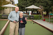 A couple playing bocce ball looking at camera.