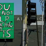 Markus Meinhardt, an employee of Electrical Systems, Inc., glanced towards an art installation while installing traffic signals at the corner of 43rd and Main Street in Kansas City, Mo. The art, created by artist David Shrigley of Glasgow, Scotland, dares the viewer not to notice the installation fixed to the west side of the H&R Block Artspace at the Kansas City Art Institute.