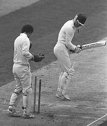 Surrey wicket-keeper Jack Richards (l) watches as Nottinghamshire County Cricket Club captain Clive Rice turns to see the ball part his wicket during the Schweppes County Championship game at The Oval.