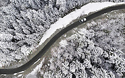 Image of a White 1993 Porsche 968 driving through a winter landscape of Evergreen firs in North Bend, North Cascades, Washington, Pacific Northwest by Randy Wells