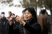 Woman takes a photograph at The Summer Palace, Beijing, China