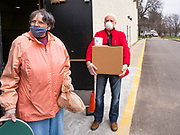 06 APRIL 2020 - DES MOINES, IOWA: LAURIE HICKS and LARRY CLAUSON, both volunteers, wait for a car to drive up during an emergency food distribution at First DSM Church in Des Moines. On Monday, 06 April, Iowa reported 946 confirmed cases of the Novel Coronavirus (SARS-CoV-2) and COVID-19. There have been 25 deaths attributed to COVID-19 in Iowa. Most non-essential businesses are closed until 30 April. Well over 100,000 Iowans filed first time claims for unemployment in the last three weeks, more than applied during the peak of the Great Recession of 2008. Local food banks have seen an equal spike in people seeking nutritional assistance. First DSM Church has increased their food pantry from one day weekly to three days per week. Hundreds of people lined up Monday to get a box of food and one roll of toilet paper at the church's drive through pantry.          PHOTO BY JACK KURTZ