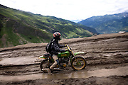 A day-tourist riding a bike is having a hard time along a wet and particularly muddy section of the Leh-Manali Highway leading up to Rotanlg La, (3,978 m) the nearest pass to the hill station of Manali, in Himachal Pradesh, 600 km north of New Delhi...The Leh-Manali Highway is the main road connection between the remote mountainous region of Ladhak, with capital in Leh (3300m), and Manali, HP, a famous hill station 600 km north of New Delhi. Open only four months a year, it is the second-highest motorable road in the world crossing passes up to 5300 meters. It was constructed by the Indian Army in order to develop the surrounding areas as well as monitoring the nearby borders with Kashmir and China. Due to its beauty and increased accessibility, the road to Leh and Ladhak has recently become a must-see destination for local and international tourists leaving the scorching Indian plains..